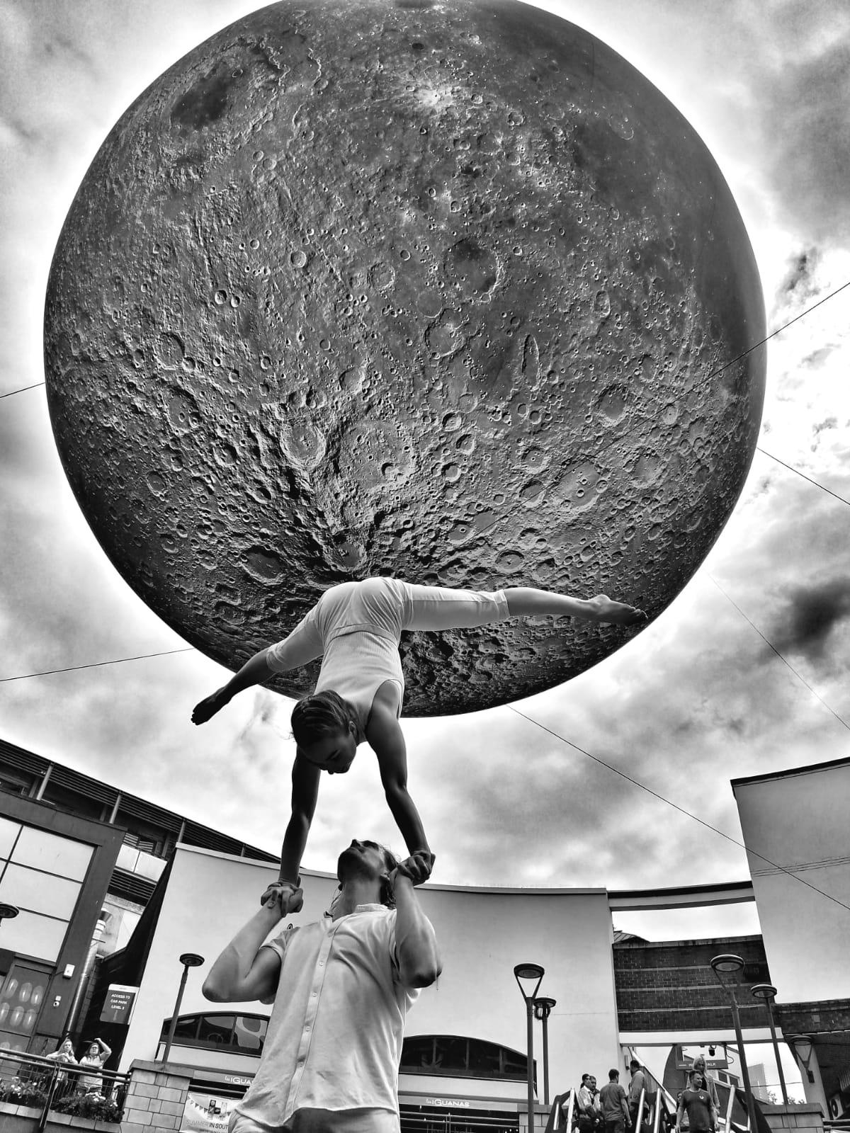 Chris and Berta performing a lift in front of the Museum of the Moon installation