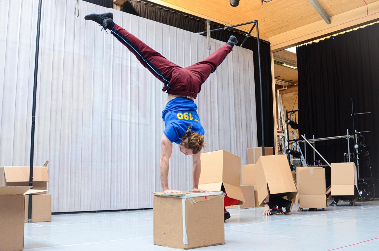 Chris in a handstand on a cardboard box