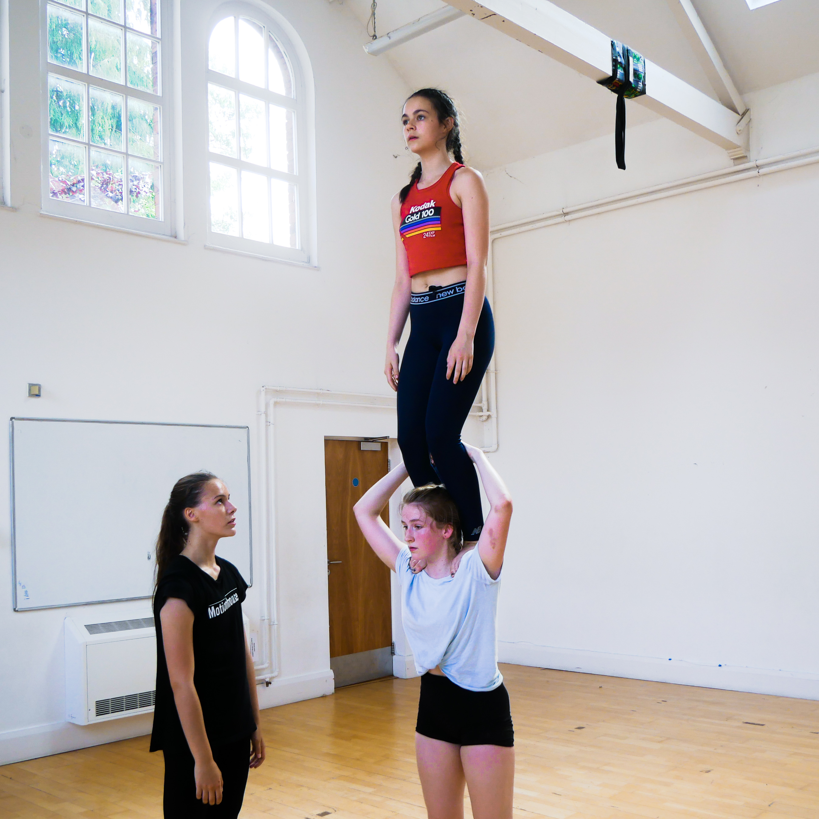 One girl stands on another shoulders in a two-high, an additional girl spots for safety.