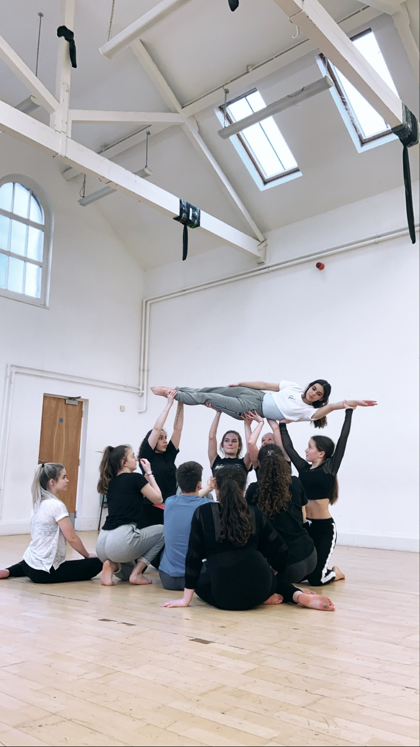 A group of teenage dancers are lifting a female dancer horizontally